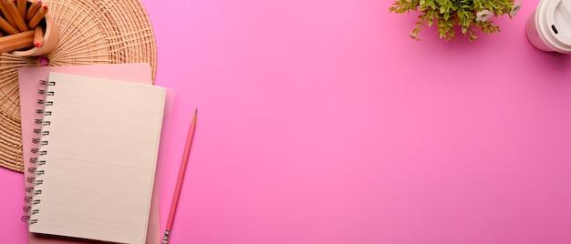 Draufsicht des rosa flachen laienarbeitsbereichs mit der dekoration des briefpapierblumentopfs und des kopierraums