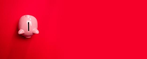 Draufsicht des rosa keramischen schweinssparschweins auf einem roten hintergrund. geschäftsinvestitions- und -sparungskonzept