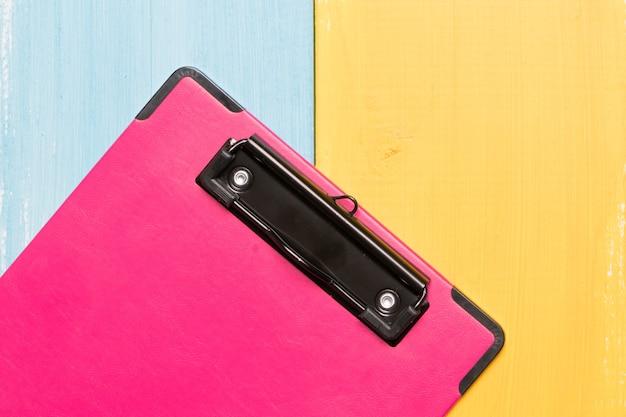 Draufsicht des rosa klemmbrettes über bunte hintergründe mit kopienraum für text