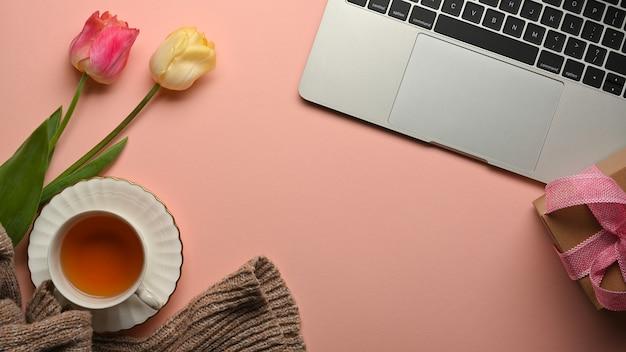 Draufsicht des rosa kreativen arbeitsbereichs mit teetasse, blumen, laptop und kopierraum im arbeitszimmer zu hause