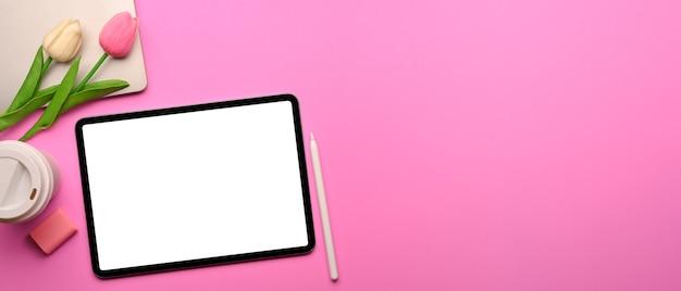 Draufsicht des rosa kreativen flachen laienarbeitsbereichs mit digitalem tablett liefert tulpenblumen und kopierraum Premium Fotos