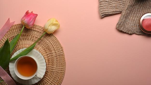 Draufsicht des rosa tisches mit tae tasse, blumen, pullover und kopienraum im wohnzimmer