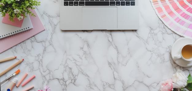 Draufsicht des rosa weiblichen designerarbeitsplatzes mit laptop-computer und malwerkzeugen auf marmorschreibtisch