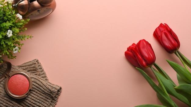 Draufsicht des rosa weiblichen kreativen flachen flachen arbeitsbereichs mit blumen, kosmetik, dekorationen und kopierraum