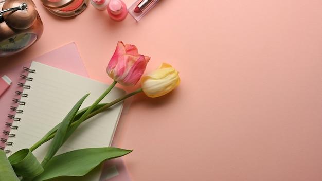 Draufsicht des rosa weiblichen kreativen flachen laienarbeitsbereichs mit blumen, notizbuch und kosmetik auf dem tisch