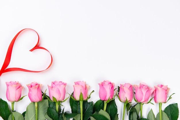 Draufsicht des roten herzens und des rahmens der rosa rosen auf weißem hintergrund. valentinstag konzept.