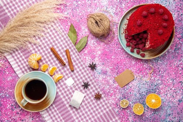 Draufsicht des roten himbeerkuchens mit zimt-mandarinen und tasse tee auf rosa oberfläche