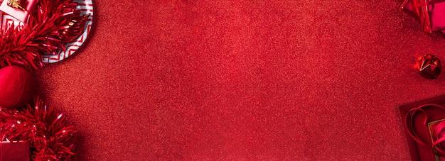 Draufsicht des roten hintergrundes der frohen weihnachten und des neuen jahres des lamettas, geschenk, ball, band verzieren auf tabelle