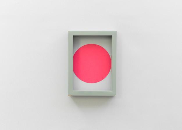 Draufsicht des roten papierausschnitts mit leerem leerem fotorahmen an lokalisiert auf weißem hintergrund