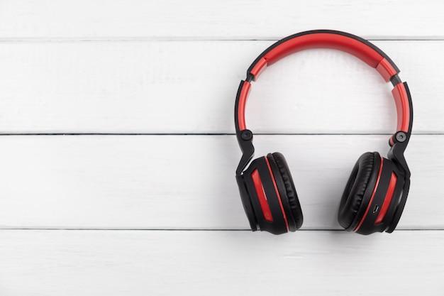 Draufsicht des roten und schwarzen kopfhörers auf weißem tisch