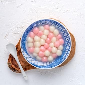 Draufsicht des roten und weißen tangyuan (tang yuan, klebreisknödelbällchen) in der blauen schüssel auf weißem hintergrund für wintersonnenwende-festessen.