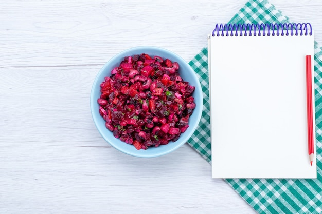 Draufsicht des rübensalats, der mit grüns innerhalb der blauen platte mit notizblock auf hellem schreibtisch geschnitten wird, salatgemüselebensmittelmahlzeitgesundheit