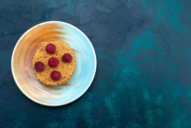 Draufsicht des runden kuchens mit frischen himbeeren innerhalb platte auf der dunkelblauen oberfläche
