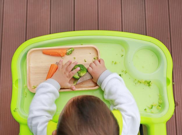 Draufsicht des säuglingsbabys essend durch baby geführtes entwöhnen (blw). fingerfood-konzept.