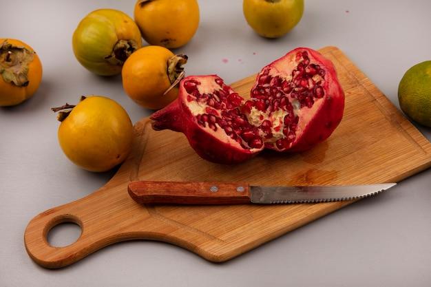 Draufsicht des saftigen halbierten granatapfels auf einem hölzernen küchenbrett mit messer mit kaki-früchten isoliert