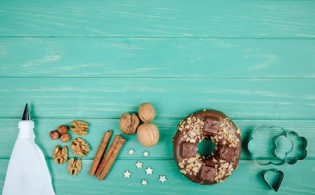 Draufsicht des sahneinjektors mit nuss-zimt-keks und verschiedenen dekoren auf grün mit kopienraum