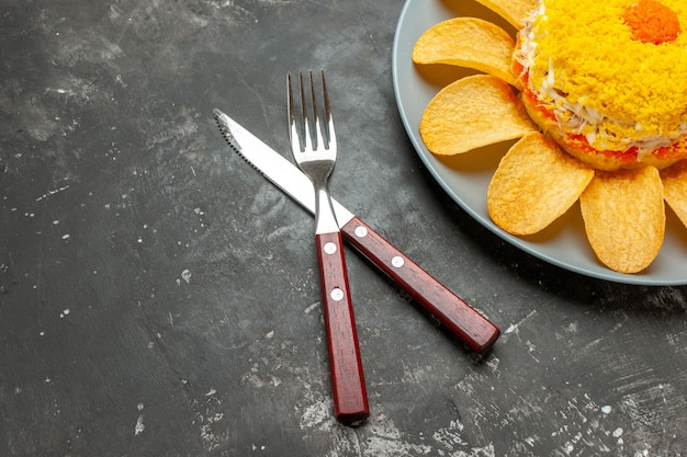 Draufsicht des salats auf der rechten oberen seite mit gekreuzter gabel und messer auf der seite auf schwärzlichem hintergrund Kostenlose Fotos