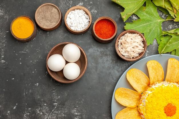 Draufsicht des salats auf der unterseite mit kräuterschale von eiern und blättern auf seite auf dunkelgrauem hintergrund