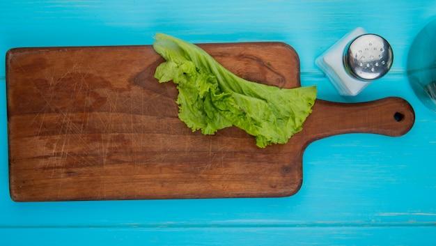 Draufsicht des salats auf schneidebrett mit salz auf blauer oberfläche