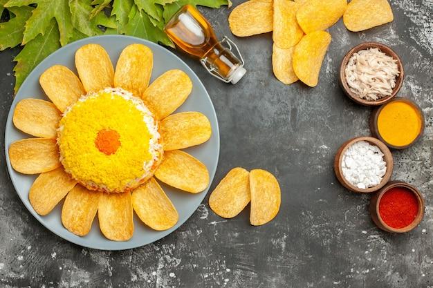 Draufsicht des salats mit den knusprigen pommes frites der ölflasche und den blättern auf der seite mit kräutern nahe auf dem dunkelgrauen tisch