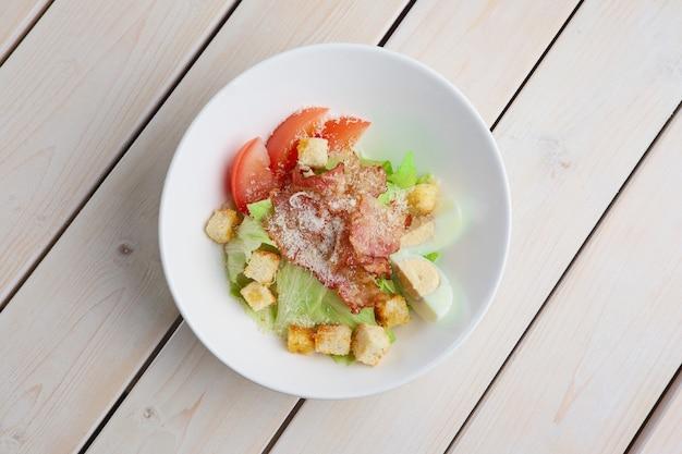 Draufsicht des salats mit gegrilltem speck, crackern, ei, tomate und käse