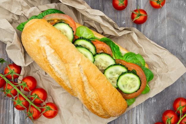 Draufsicht des sandwichs auf papier mit tomaten und gurkenscheiben