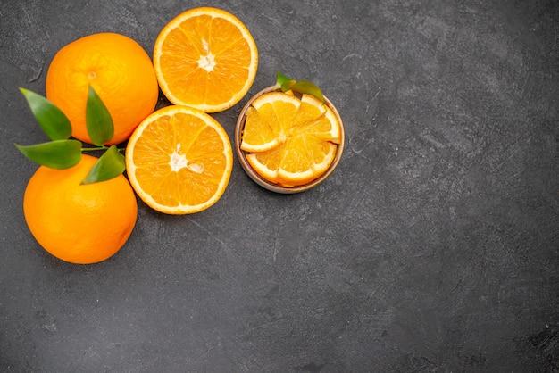 Draufsicht des satzes von gelben ganzen und gehackten orangen auf dunklem tisch