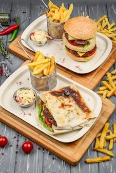 Draufsicht des schnellimbiss-tellers. fleischburger, kartoffelchips und keile.