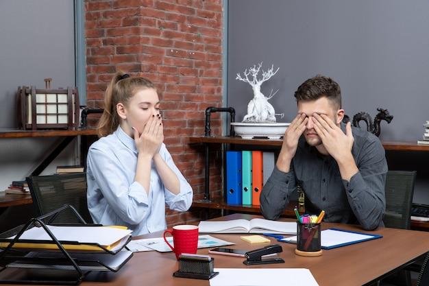 Draufsicht des schockierten büroteams, das am tisch sitzt und ein wichtiges thema im büro diskutiert