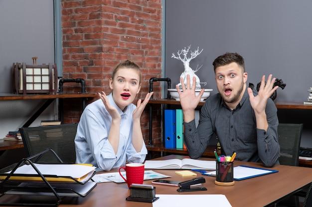 Draufsicht des schockierten büroteams, das am tisch sitzt und für die kamera im büro posiert