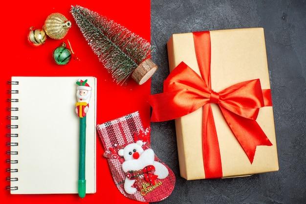 Draufsicht des schönen geschenkweihnachtsbaumsocken-notizbuchs mit stift auf rotem und schwarzem hintergrund