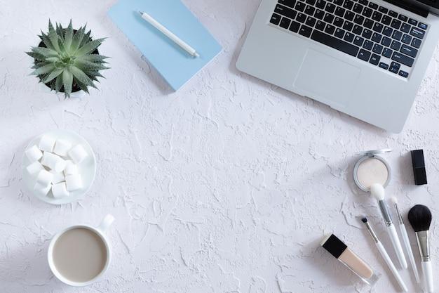Draufsicht des schönheitsblogger-arbeitsschreibtischs mit laptop, notizbuch, dekorativer kosmetik, blumen und kaffeetasse, umschlag auf weißer pastelltabelle. flach lag hintergrund.