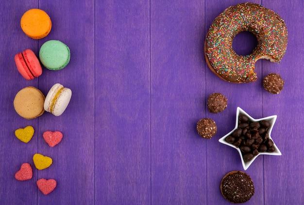 Draufsicht des schokoladendonuts mit marmeladenschokoladenbonbons und macarons auf einer hellvioletten oberfläche