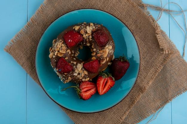 Draufsicht des schokoladenkrapfen mit erdbeeren auf einem blauen teller auf einer beigen serviette auf einer blauen oberfläche