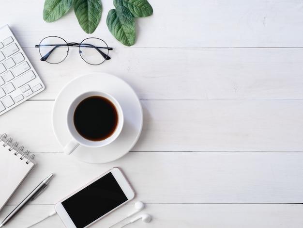 Draufsicht des schreibtischarbeitsplatzes auf weißem holztischhintergrund