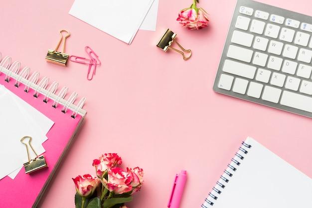Draufsicht des schreibtischbriefpapiers mit blumenstrauß von rosen