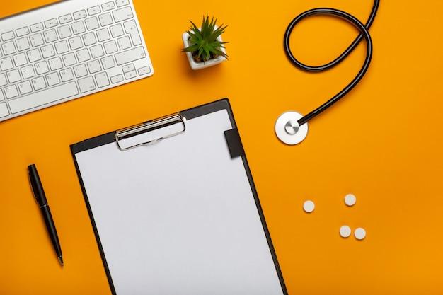 Draufsicht des schreibtisches doktors mit stethoskoptastaturnotizblock und -stift