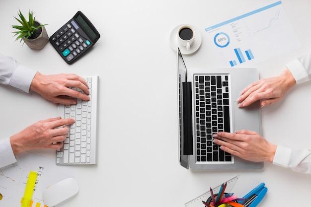 Draufsicht des schreibtisches mit den händen, die an laptop und tastatur arbeiten