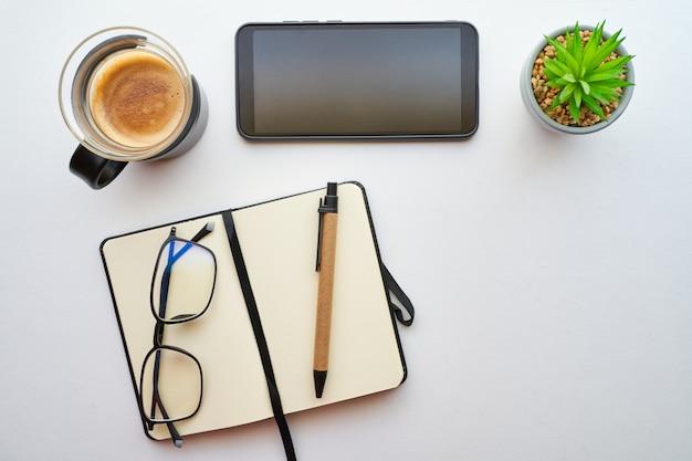 Draufsicht des schreibtisches mit einem couchtisch, einem handy, einem notizbuch und einem stift. konzept, planung und produktivität des heimstudiums.