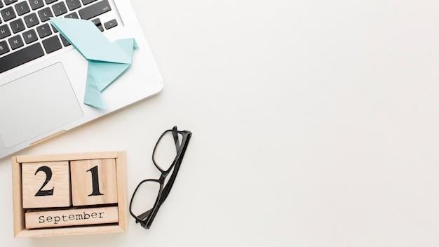 Draufsicht des schreibtisches mit kalender und papiertaube