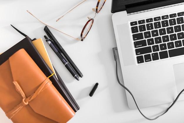 Draufsicht des schreibtisches mit laptop und brille