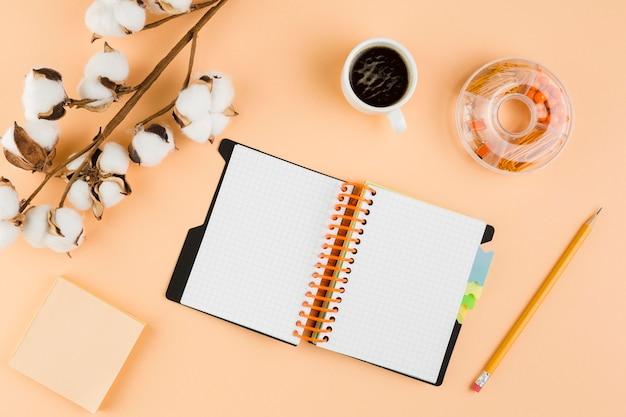 Draufsicht des schreibtisches mit notizbuch und baumwolle