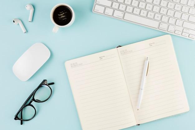 Draufsicht des schreibtisches mit notizbuch und tastatur