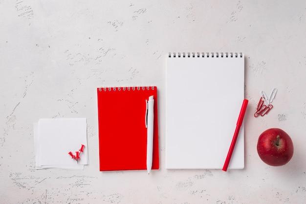 Draufsicht des schreibtisches mit notizbüchern und apfel