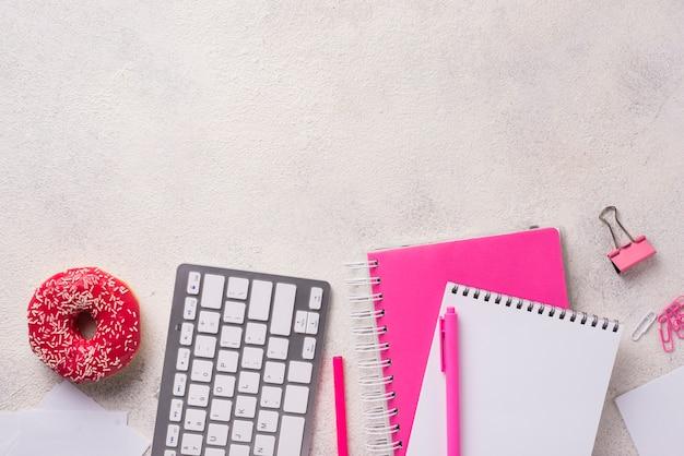 Draufsicht des schreibtisches mit notizbüchern und donut