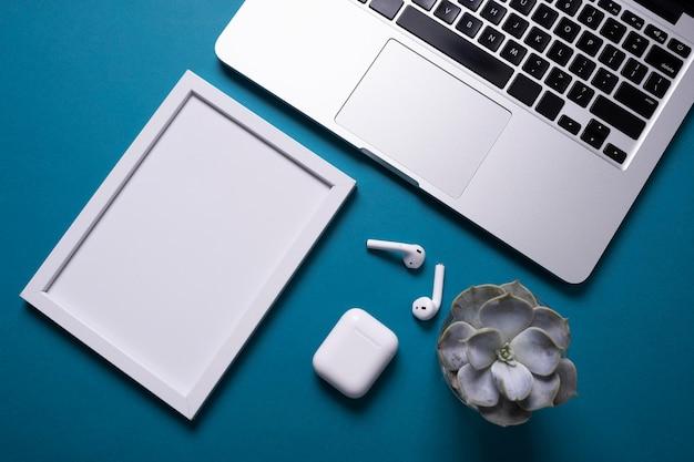 Draufsicht des schreibtisches mit rahmen und laptop