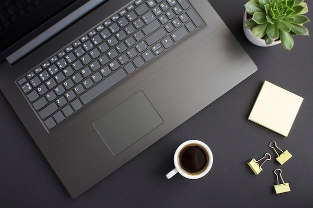Draufsicht des schreibtischs mit laptop und kaffeetasse auf dem schwarzen tisch. flache lage des arbeitsbereichs schreibtisch.