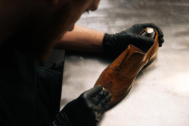 Draufsicht des schusters mit schwarzen latexhandschuhen, der alte hellbraune lederschuhe mit lappen reinigt