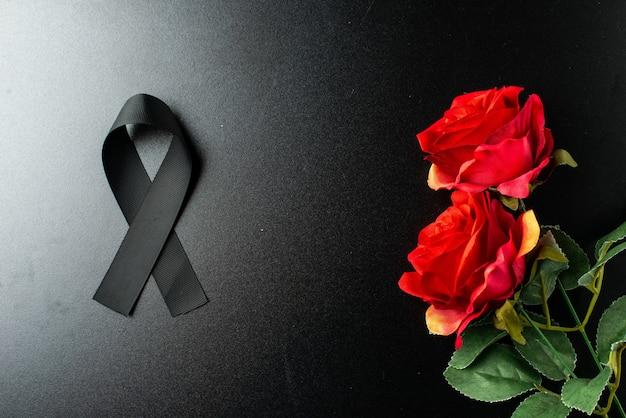Draufsicht des schwarzen bogens als trauersymbol mit roter rose an dunkler wand