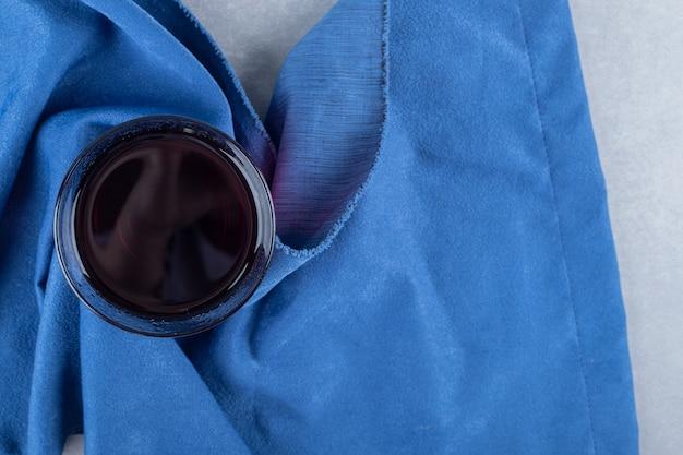 Draufsicht des schwarzen kaffees im glas auf blau